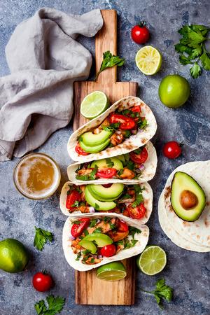 Tacos mexicanos de pollo a la parrilla con aguacate, tomate, cebolla sobre mesa de piedra rústica. Receta para la fiesta del Cinco de Mayo. Vista superior, aérea, endecha plana. Foto de archivo