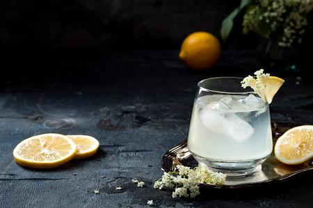 A glass of homemade elderflower gin sour or lemonade garnished with freshly picked elderflowers.