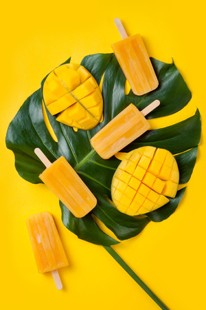 Mango popsicles over green tropical palm leaf on yellow colored background. Minimal flat lay style. Overhead, top view