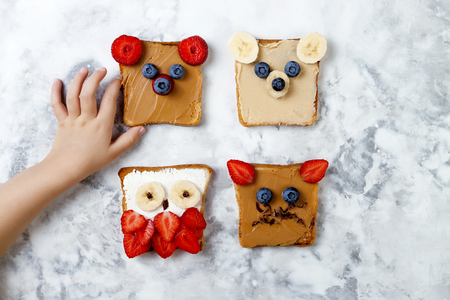 Healthy funny face sandwiches for kids. Animal faces toast with peanut and cashew butter, ricotta cheese, banana, strawberry and blueberry Stock Photo