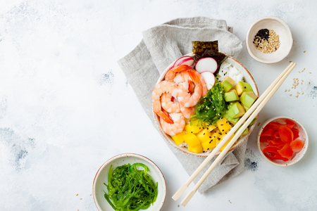 Hawaiian shrimp poke bowl with seaweed, avocado, mango, pickled ginger, sesame seeds. Top view, overhead, flat lay, copy space