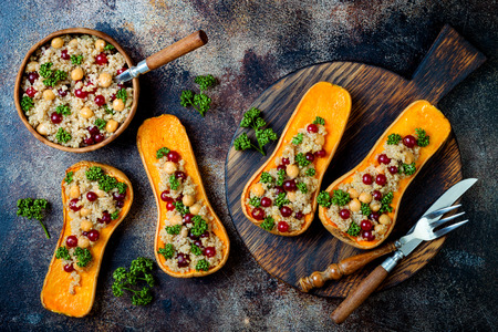 Stuffed butternut squash with chickpeas, cranberries, quinoa cooked in nutmeg, cloves, cinnamon. Thanksgiving dinner recipe. Vegan healthy seasonal fall or autumn food Фото со стока