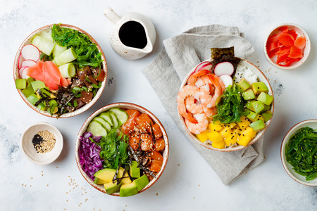 Hawaiian salmon, tuna and shrimp poke bowls with seaweed, avocado, mango, pickled ginger, sesame seeds. Top view, overhead, flat lay 免版税图像 - 108251789