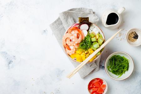 Hawaiian shrimp poke bowl with seaweed, avocado, mango, pickled ginger, sesame seeds. Top view, overhead, flat lay, copy space