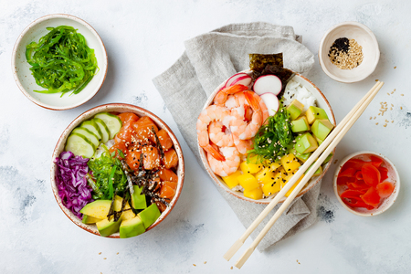 Hawaiian salmon and shrimp poke bowls with seaweed, avocado, mango, pickled ginger, sesame seeds. Top view, overhead, flat lay Imagens
