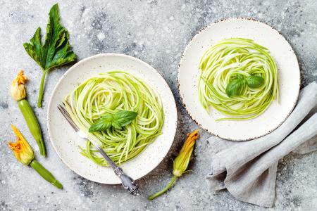 Courgettespaghetti met basilicum. Vegetarische plantaardige koolhydraatarme pasta. Courgette noedels of zoodles. Stockfoto
