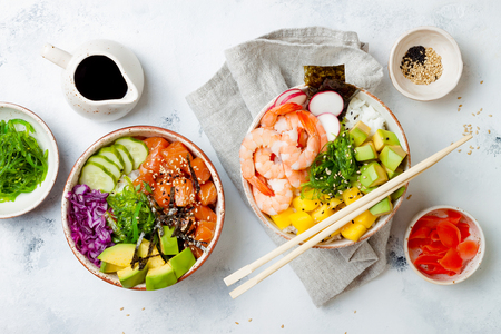 Hawaiian salmon and shrimp poke bowls with seaweed, avocado, mango, pickled ginger, sesame seeds. Top view, overhead, flat lay Stock Photo