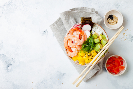 Hawaiian shrimp poke bowl with seaweed, avocado, mango, pickled ginger, radish, sesame seeds. Top view, overhead, flat lay, copy space Imagens