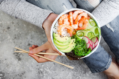 Girl in jeans holding shrimp poke bowl with seaweed, avocado, cucumber, radish, sesame seeds.