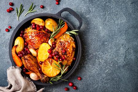 Cosce di pollo arrosto con ortaggi a radice, limone, aglio, mirtillo rosso e rosmarino in padella, su fondo di pietra di ardesia nera