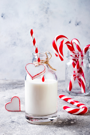 Christmas milk for Santa in bottle with straw and peppermint candy cane. Christmas holiday party drink idea Stock Photo