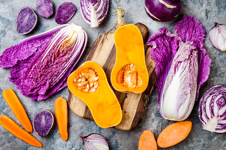 Seasonal winter autumn fall vegetables over gray stone table. Plant based vegan or vegetarian cooking concept. Clean eating food, alkaline diet