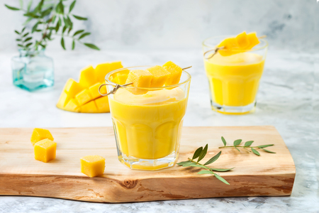 Mango Lassi, yogurt or smoothie with turmeric. Healthy probiotic Indian cold summer drink Imagens - 113907531