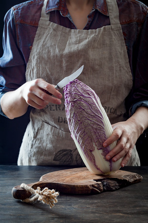 Woman cutting purple cabbage for kimchi recipe. Fermented and vegetarian probiotic food for gut health Stock Photo