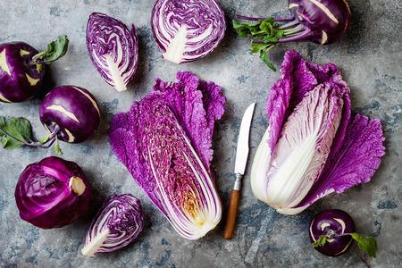Seasonal winter autumn purple vegetables over gray stone table. Plant based vegan or vegetarian cooking concept. Clean eating food, alkaline diet
