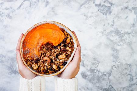 Woman in woolen sweater holding bowl with cinnamon granola, coconut yogurt, chia seeds and pumpkin puree. Healthy vegan, vegetarian breakfast smoothie bowl Stock Photo