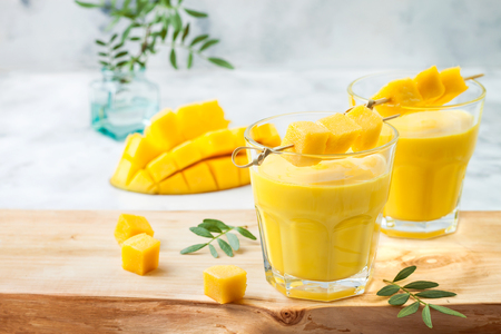 Mango Lassi, yogurt or smoothie with turmeric. Healthy probiotic Indian cold summer drink 免版税图像