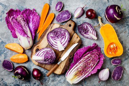 Seasonal winter autumn fall vegetables over gray stone background. Plant based vegan or vegetarian cooking concept. Clean eating food, alkaline diet