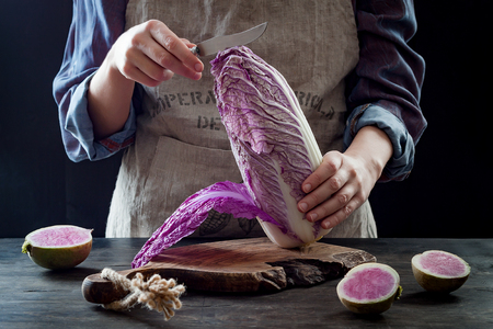 Cabbage and watermelon radish kimchi ingredients. Woman cutting purple cabbage for kimchi recipe. Fermented and vegetarian probiotic food for gut health