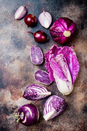 Seasonal winter autumn purple vegetables on rustic background. Plant based vegan or vegetarian cooking concept. Clean eating food, alkaline diet