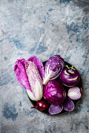 Seasonal winter autumn purple vegetables over gray stone background. Plant based vegan or vegetarian cooking concept. Clean eating food, alkaline diet