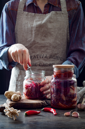 Cabbage kimchi in glass jar. Woman preparing purple cabbage and watermelon radish kimchi. Fermented and vegetarian probiotic food for gut health