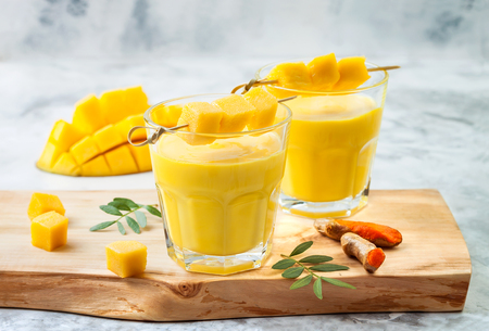 Mango Lassi, yogurt or smoothie with turmeric. Healthy probiotic Indian cold summer drink Stock Photo