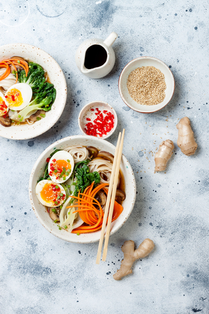 Ramen traditional Japanese noodle soup with eggs, pak choi cabbage, meat broth, carrot, mushrooms in bowl on light grey