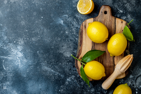 Fresh ripe lemons with leaves on wooden board with  reamer over black stone Archivio Fotografico - 117900016