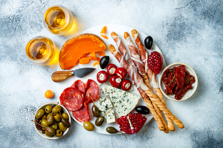 Appetizers table with antipasti snacks and wine in glasses. Authentic traditional spanish tapas set, cheese