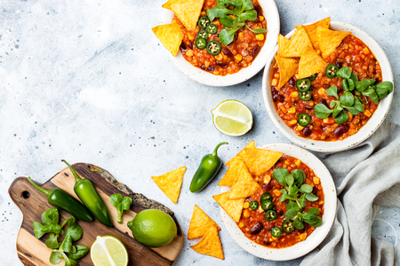 Vegetarian chili con carne with lentils, beans, nachos, lime, jalapeno. Mexican traditional dish