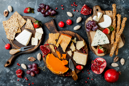 Cheese variety board or platter with cheese assortment, grapes, honey, nuts.