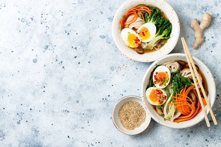 Ramen traditional japanese noodle soup with eggs, pak choi cabbage, meat broth, carrot, mushrooms in bowl on light grey Stock Photo