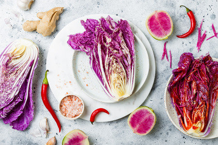 Cabbage kimchi, top view. Preparing purple cabbage and watermelon radish kimchi. Fermented and vegetarian probiotic food for gut health Stock Photo