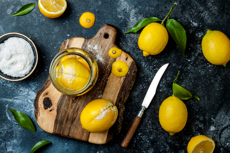 Preserved, salted canned lemons on a wooden board over black stone