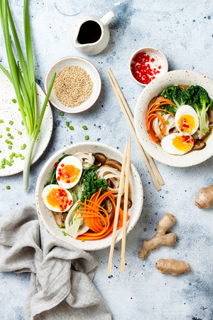 Ramen traditional japanese noodle soup with eggs, pak choi cabbage, meat broth, carrot, mushrooms in bowl on light grey Stockfoto
