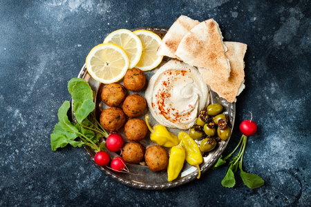 Middle Eastern meze platter with falafel, pita,  hummus, pickles, radishes. Mediterranean or greek appetizer party idea