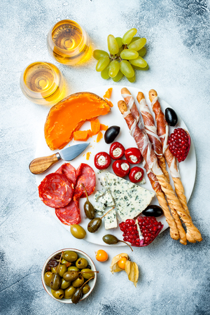 Appetizers table with antipasti snacks and wine in glasses. Reklamní fotografie