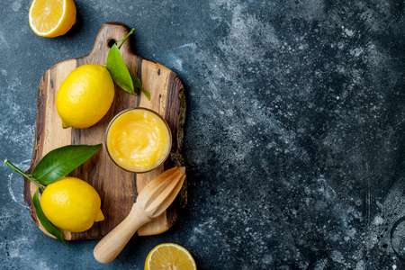 Lemon curd in a glass jar with fresh lemons. Top view