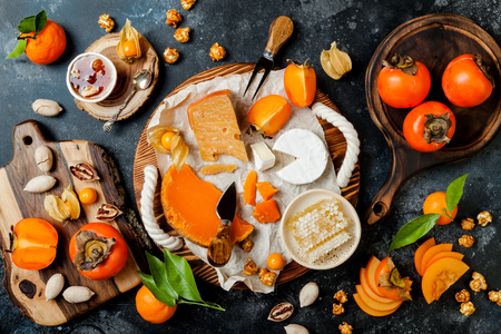 Cheese variety board or platter with cheese assortment, persimmons, honey and nuts.
