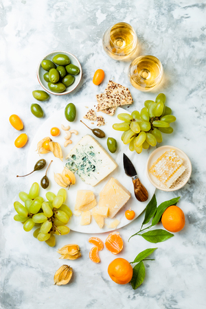 Cheese platter with different cheeses, grapes, nuts, honey.