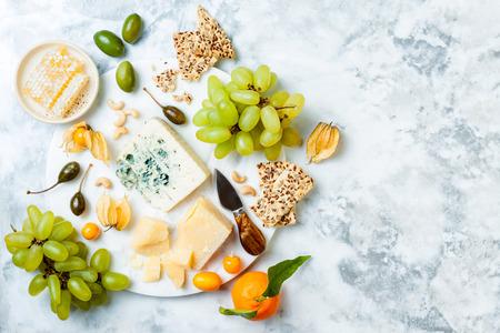 Tabla de quesos con diferentes quesos, uvas, frutos secos, miel.
