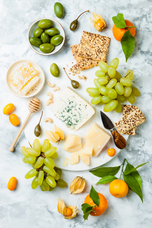 Cheese platter with different cheeses, grapes, nuts, honey. Appetizers table with antipasti snacks. Stock Photo