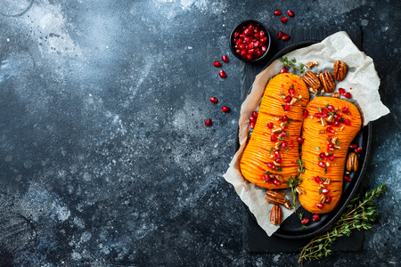 Roasted hasselback butternut squash pumpkin with thyme, pecan and pomegranate.