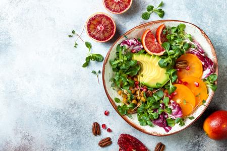 Vegan, detox Buddha bowl with turmeric roasted  chickpeas, greens, avocado, persimmon, blood orange, nuts and pomegranate.