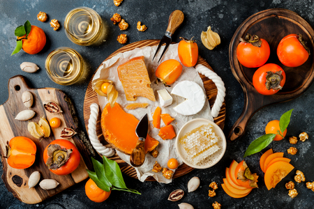 Cheese variety board or platter with cheese assortment, persimmons, honey and nuts. Black stone