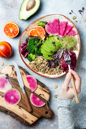 Girl holding fork and eating vegan, detox Buddha bowl with quinoa, micro greens, avocado, blood orange, broccoli, watermelon radish, alfalfa seed sprouts. Stok Fotoğraf