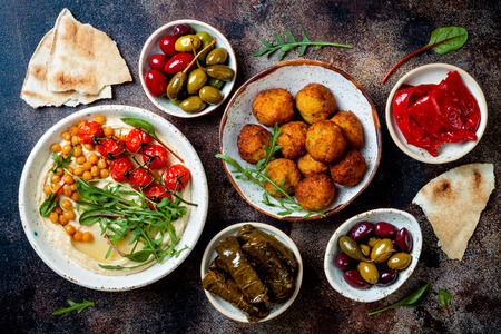 Arabic traditional cuisine. Middle Eastern meze with pita, olives, hummus, stuffed dolma, falafel balls, pickles. Mediterranean appetizer party idea