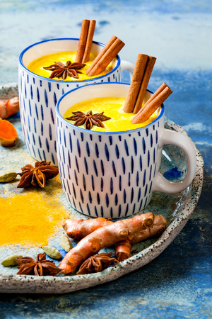 Turmeric golden milk latte with cinnamon sticks and honey. Detox, immune boosting, anti inflammatory healthy cozy drink