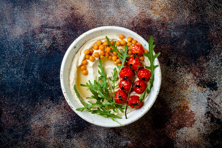 Homemade hummus with roasted cherry tomatoes. Middle Eastern traditional and authentic arab cuisine. Top view, copy space